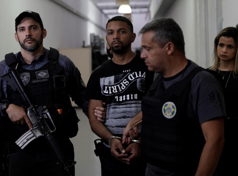 Rogerio Avelino da Silva, also known as Rogerio 157, who is accused by authorities to be the drug dealing chief of Rocinha slum, is escorted by policemen at a police station complex in Rio de Janeiro