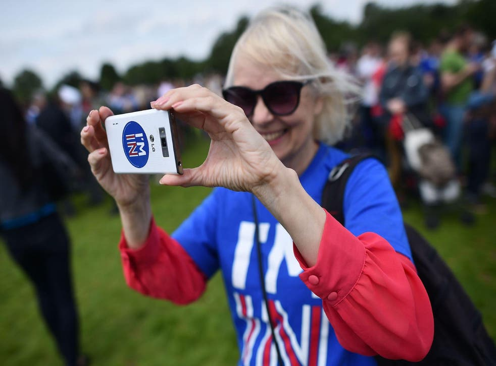 A woman uses a smartphone to take a photograph as she attends a rally for 'Britain Stronger in Europe', the official 'Remain' campaign group seeking to a avoid Brexit