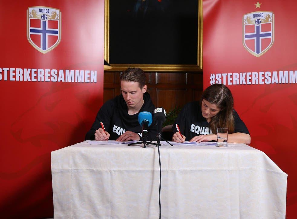 Stefan Johansen and Maren Mjelde, Norway's men's and women's captains, sign the agreement in London