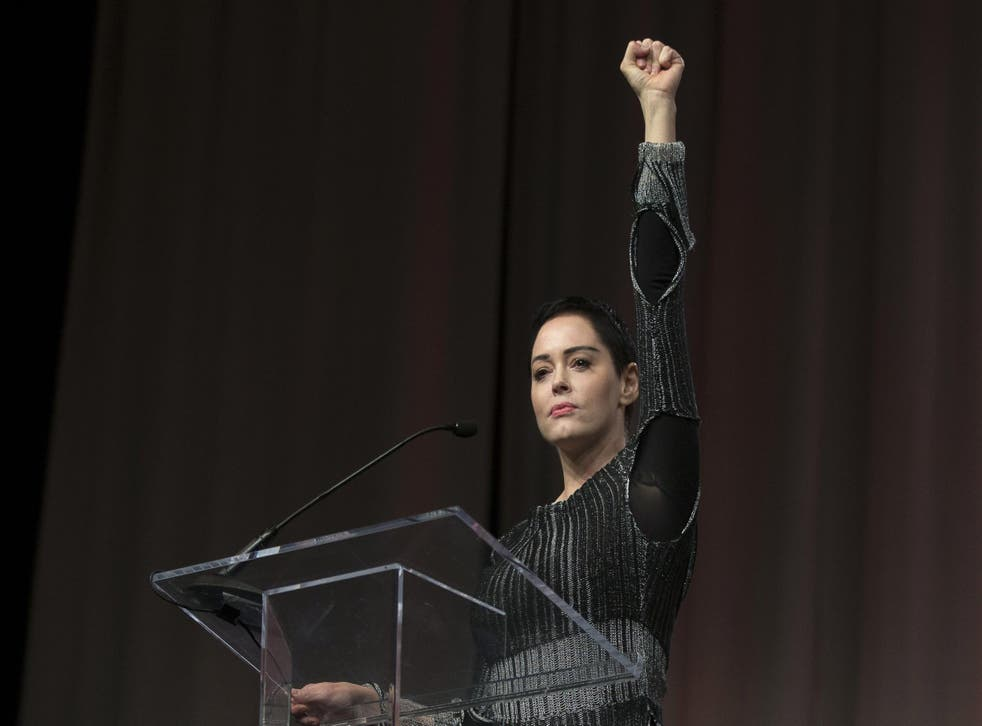 US actress Rose McGowan raises her fist during her opening remarks to the audience at the Women's March / Women's Convention in Detroit, Michigan, on October 27, 2017. Photo credit: RENA LAVERTY/AFP/Getty Images.
