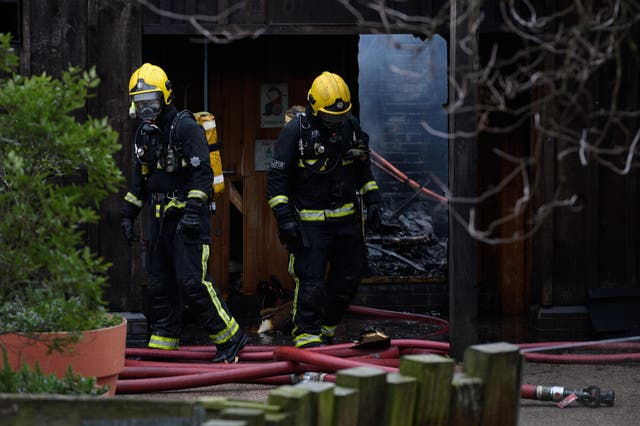 Firefighters move equipment and survey the damage after a fire destroyed buildings at London Zoo