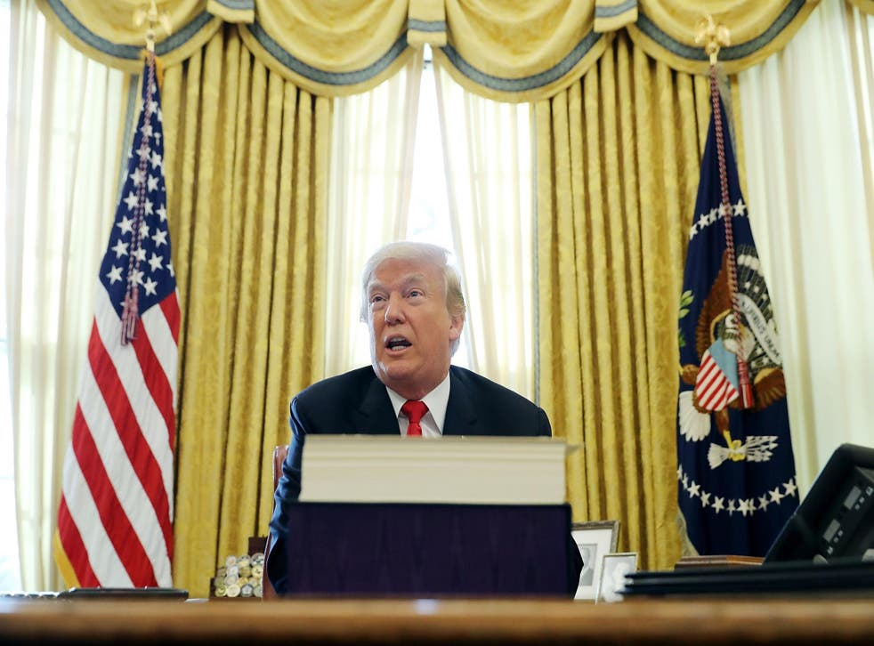 President Donald Trump talks with journalists after signing tax reform legislation into law in the Oval Office