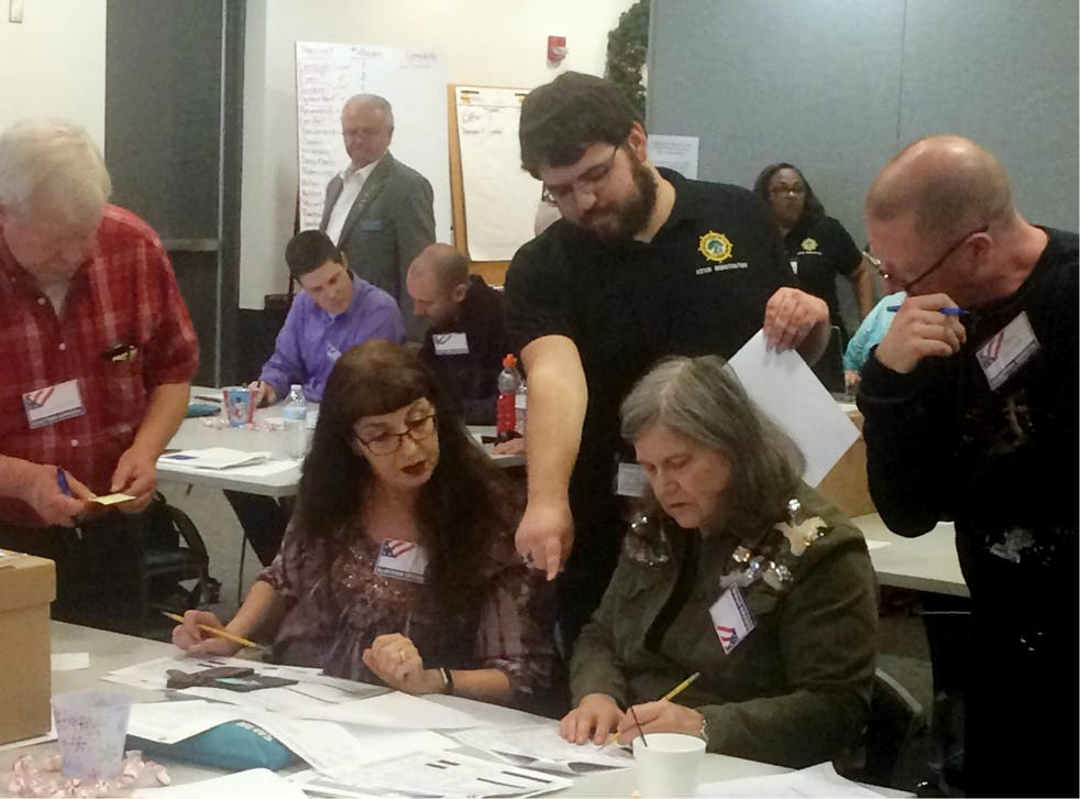 Election officials in Newport News, Virginia examine ballots that a computer failed to scan during a recount for a House of Delegates race on 19 December 2017.
