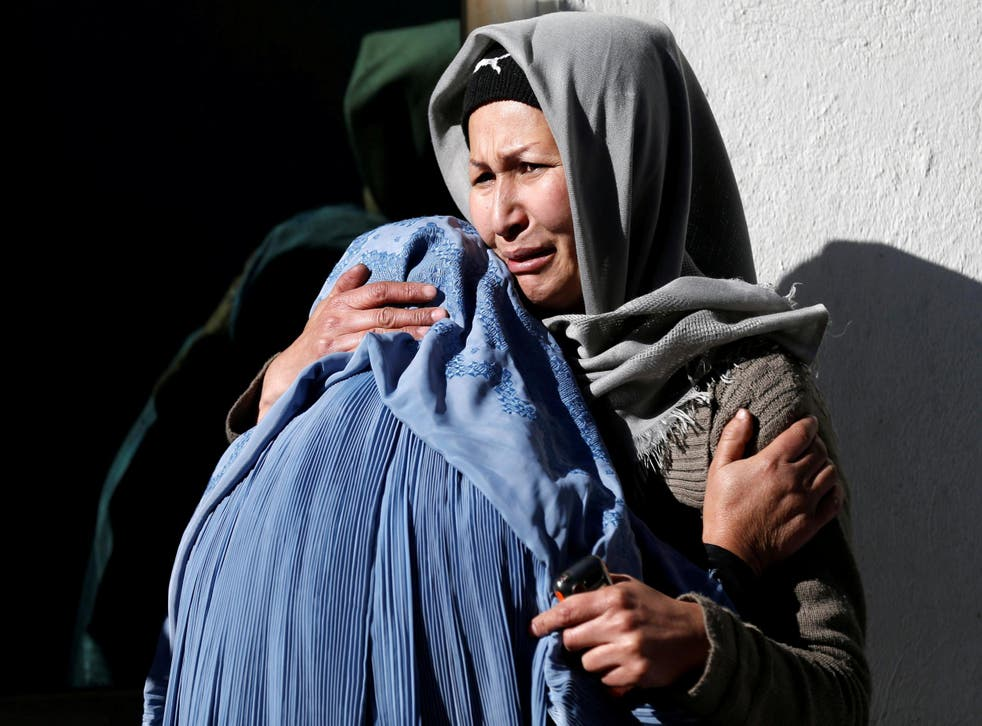 Afghan women mourn inside a hospital compound after a suicide attack in Kabul