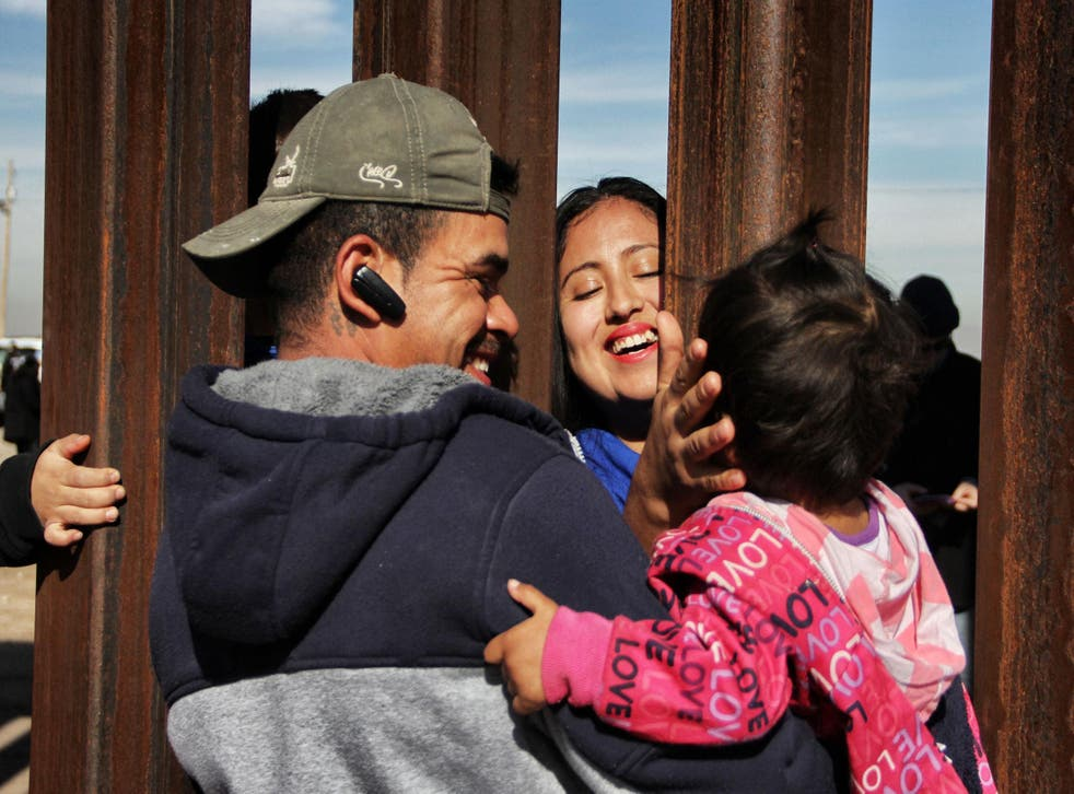 Members of a family reunite through the border wall between Mexico and United States