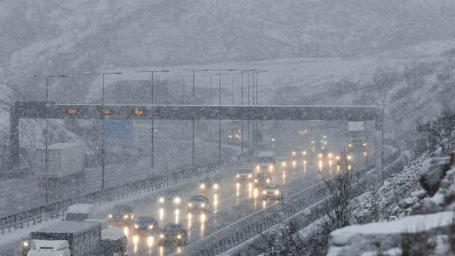 Snow causes difficult driving conditions at junction 22 of the the M62 motorway at Saddleworth in the South Pennines