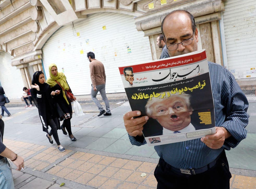 An Iranian man reads a copy of the daily newspaper 'Omid Javan' bearing a picture of US President Donald Trump with a headline that reads in Persian 'Crazy Trump'