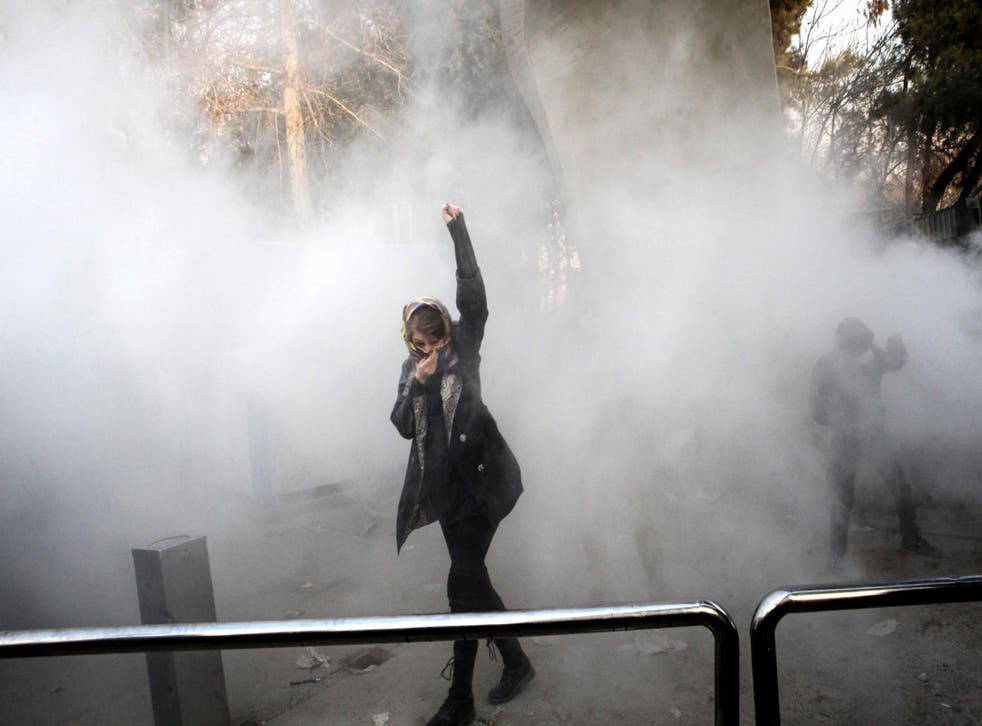 An Iranian woman raises her fist amid the smoke of tear gas at a protest at the University of Tehran