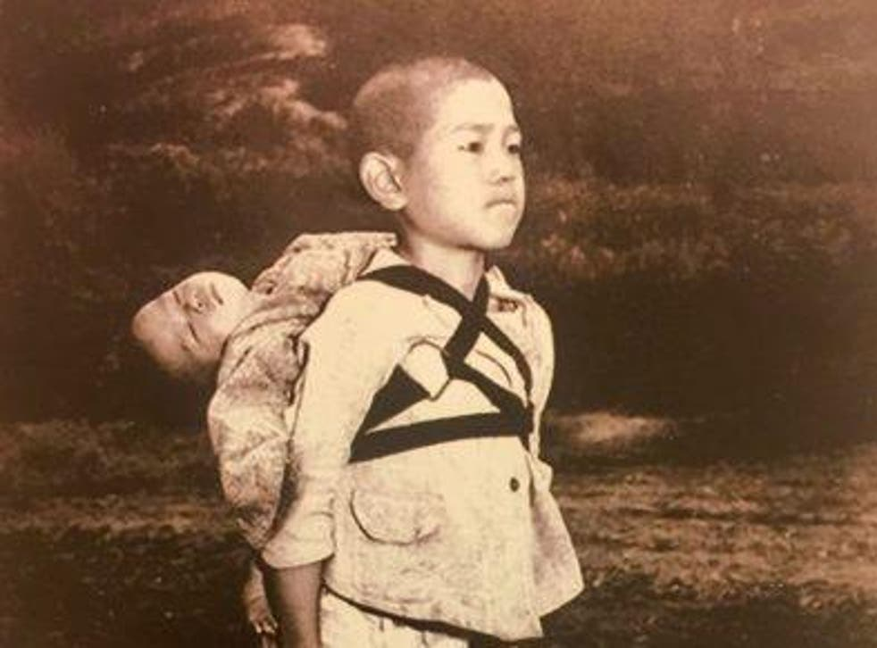A boy carries his dead brother on his shoulders while he waits at a cemetery in Nagasaki in an image taken by US Marine Joe O'Donnell in 1945
