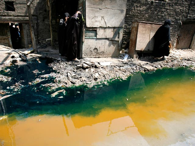 Women walk past tannery wastewater that is being pumped from a factory straight into the street, in Cairo's Ain el-Sirra district