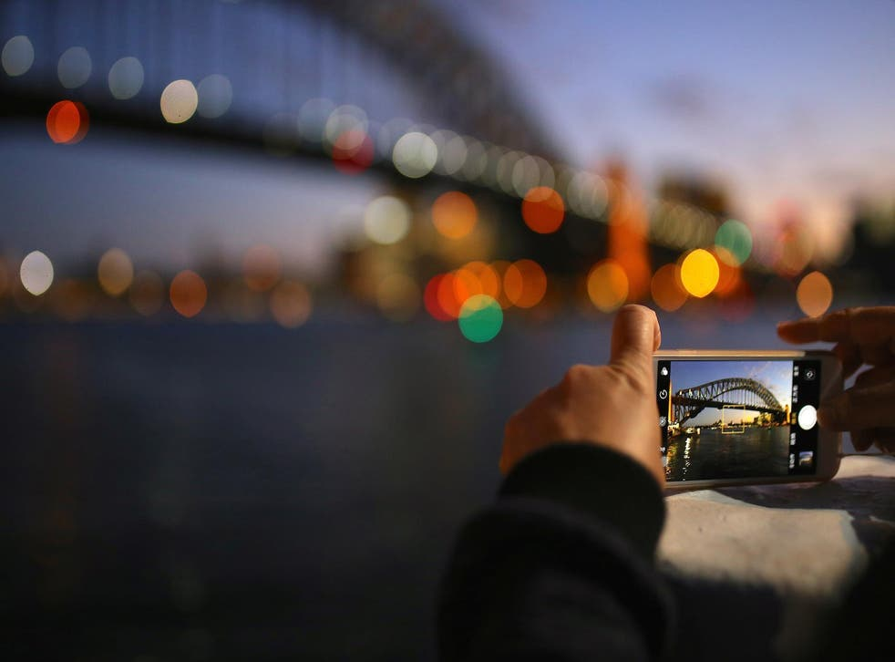 A tourist takes a photograph on their iPhone of the Sydney Harbour Bridge at sunset on a spring day in central Sydney, Australia, November 8, 2017