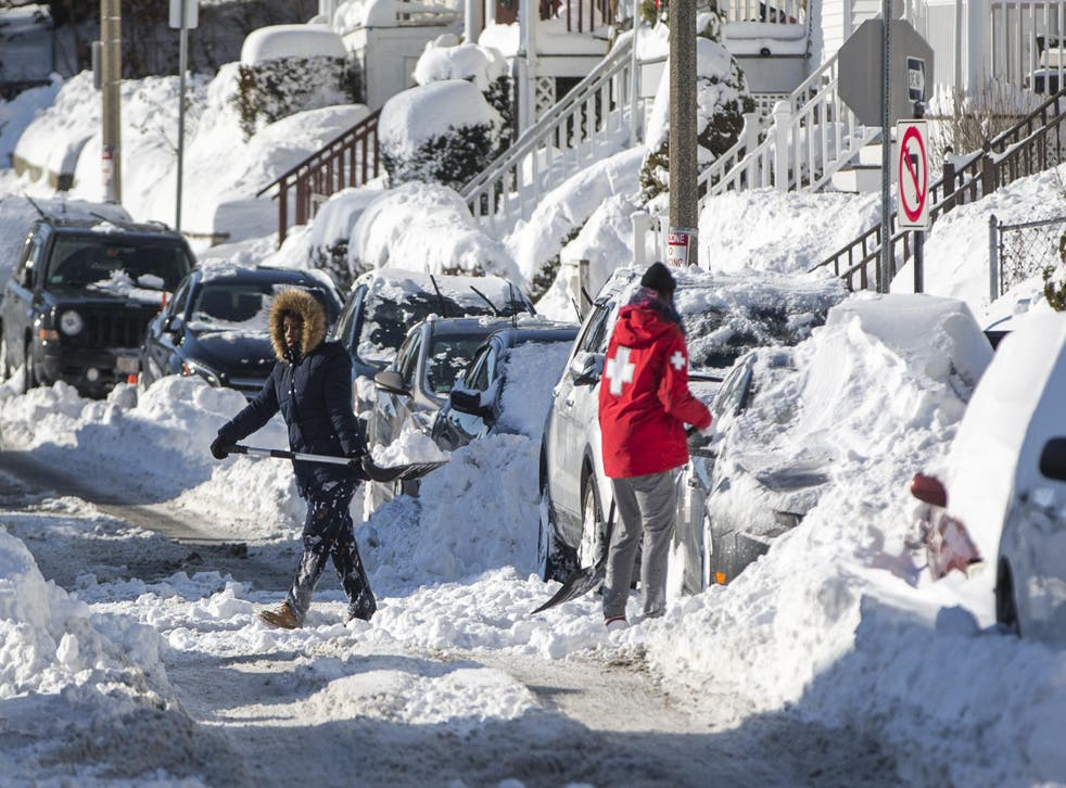 Residents in Boston, Massachusetts shovel out their vehicle the day after the region was hit with a 'bomb cyclone'