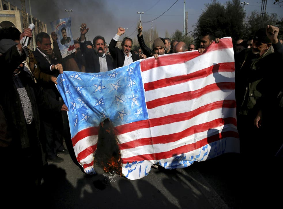Pro-government demonstrators burn a homemade US flag during a rally following a prayer ceremony in Tehran on 5 January