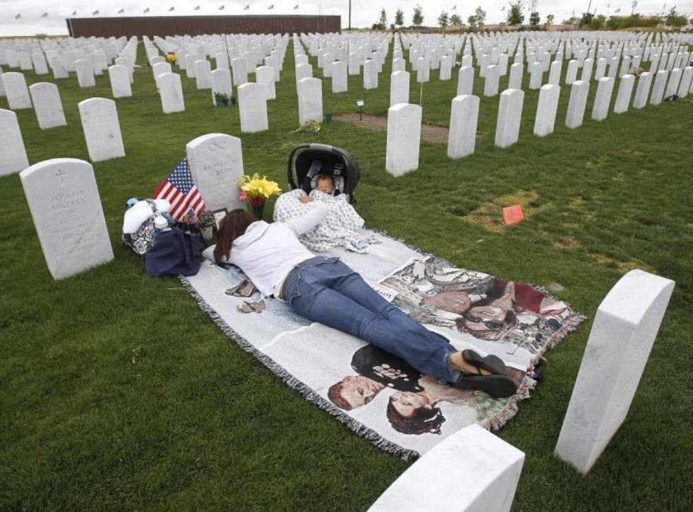 Jenn Budenz lies on a blanket with her two-month-old son, AJ, as they visit the grave of Major Andrew Budenz at Miramar National Cemetery on 22 May 2014 in San Diego