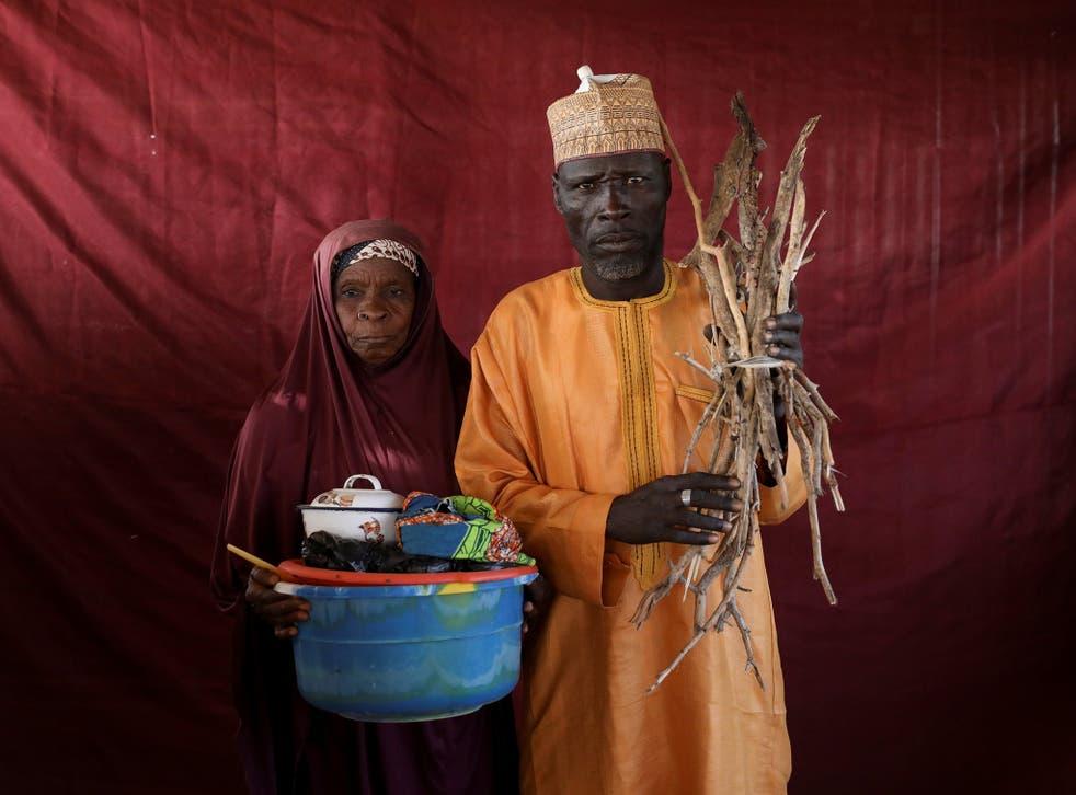 Aisha Umaru presents a basin of milk as Umari Usman Kaski holds up firewood