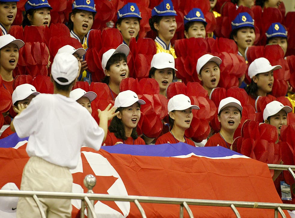 North Korean official cheerleaders sing prior to the start of the women's weight lifting final at the 14th Asian Games in 2002