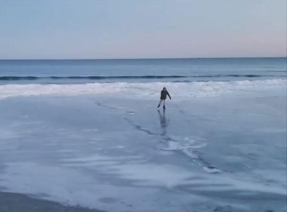 A man ice-skates on a beach in Maine as families walk on the frozen sea water