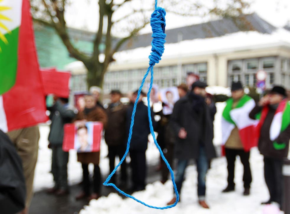 Iranian exiles shout slogans in front of a mock gallows during a demonstration in Brussels in 2010