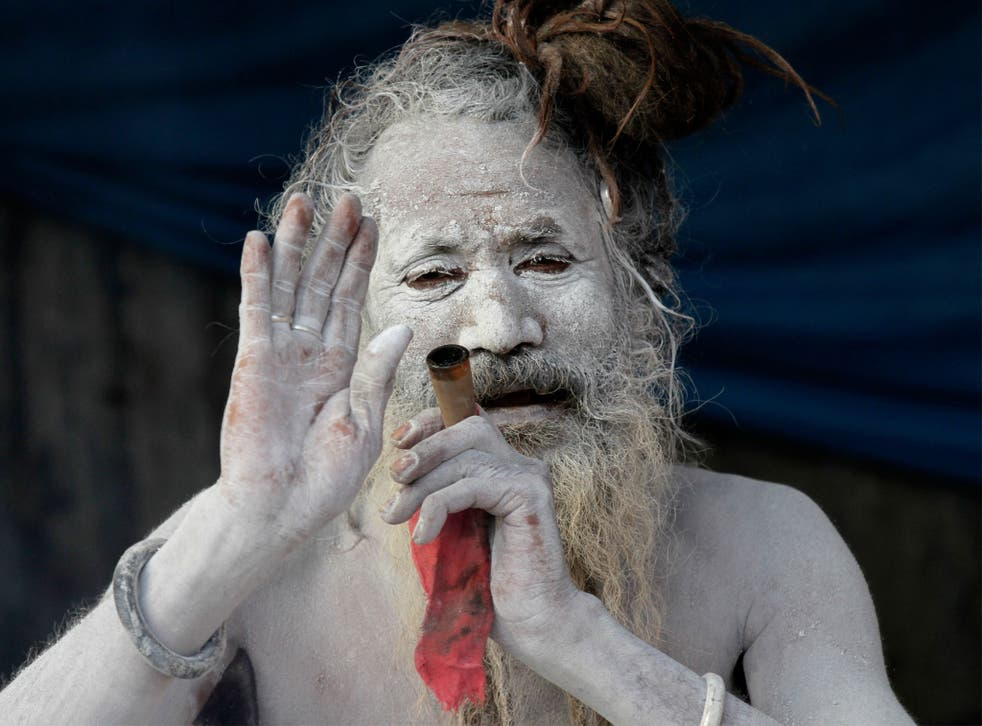 A sadhu, or a Hindu holy man, blesses a devotee as he smokes marijuana at a transit camp on the way to Gangasagar