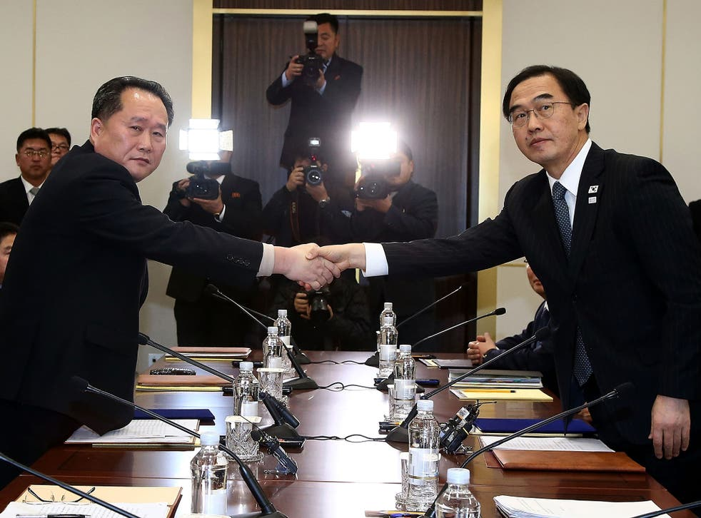 South Korean Unification Minister Cho Myoung-Gyon (R) shakes hands with the head of the North Korean delegation Ri Son-Gwon during talks this week