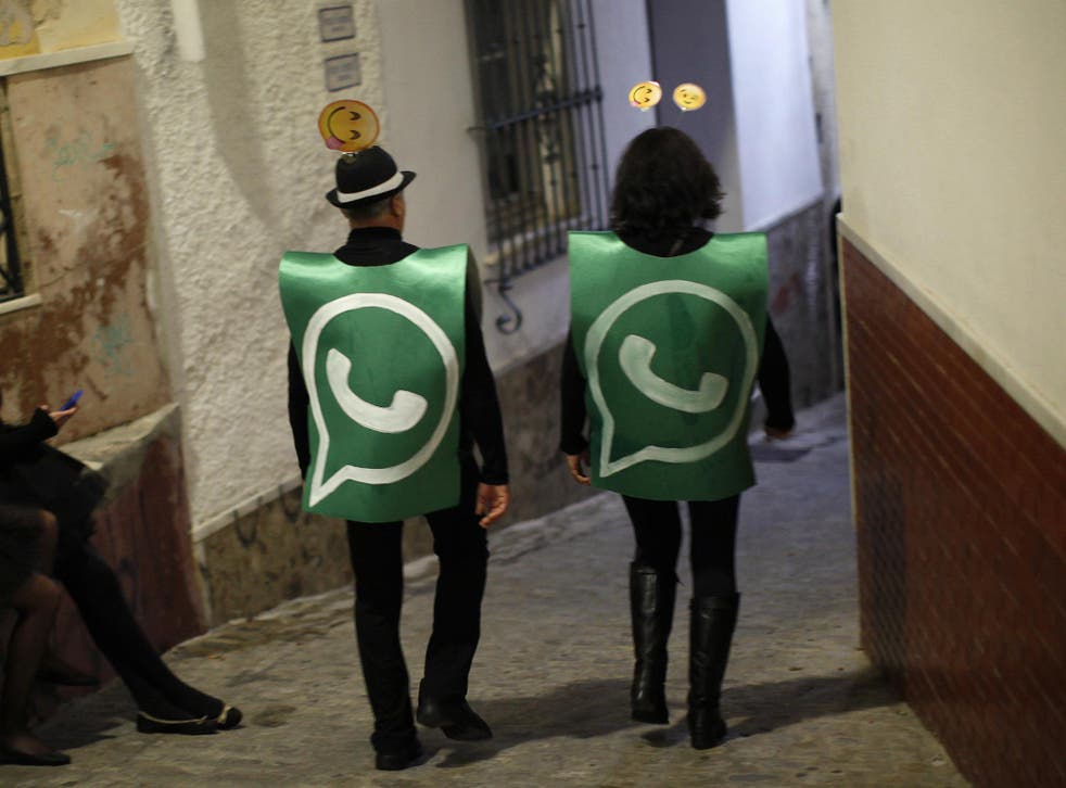 Revellers dressed up as dancers of 'Black Swan' check their mobile phones next to revellers dressed up as a Whatsapp logo as they take part in New Year's celebrations in Coin, near Malaga, southern Spain, early January 1, 2015