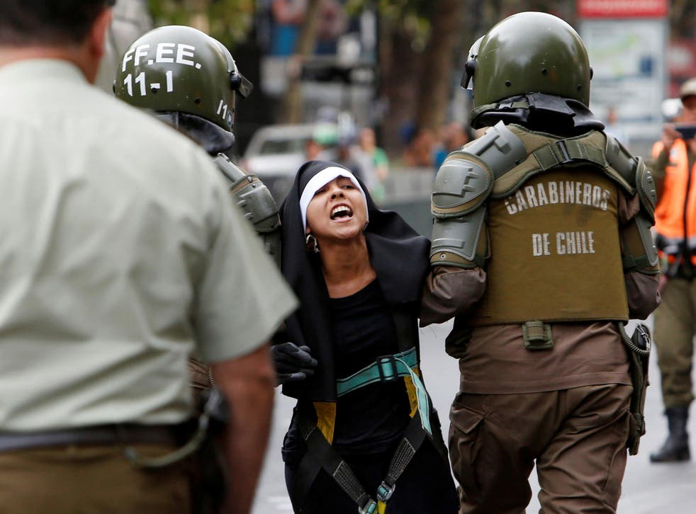 Police detain a protester dressed as a nun during the arrival of Pope Francis in Santiago
