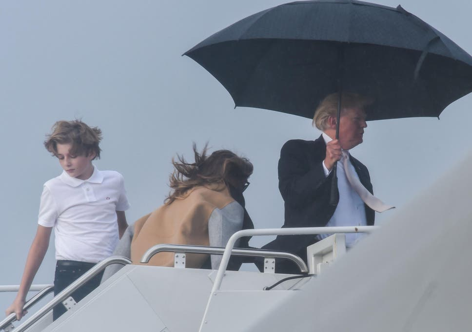 f87592c3f60ec US President Donald Trump holds an umbrella as he waits for his son Barron  and wife