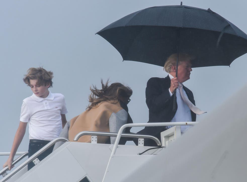 US President Donald Trump holds an umbrella as he waits for his son Barron and wife Melania to board Air Force One at Palm Beach International Airport in West Palm Beach, Florida