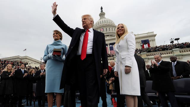 """US President Donald Trump acknowledges the audience after taking the oath of office as his wife Melania (L) and daughter Tiffany watch during inauguration ceremonies swearing in Trump as the 45th president of the United States on the West Front of the US capital in Washington on 20 January, 2017. Photographer Jim Bourg: """"This photo was shot with one of two remote cameras. The cameras were monitored and triggered remotely and the pictures were transmitted to clients worldwide within minutes of being taken."""""""
