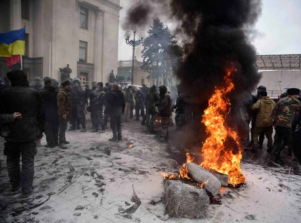 Protesters burn tyres near the Parliament building as riot policemen gather at a camp of supporters of Ukrainian opposition figure and Georgian former President Mikheil Saakashvili