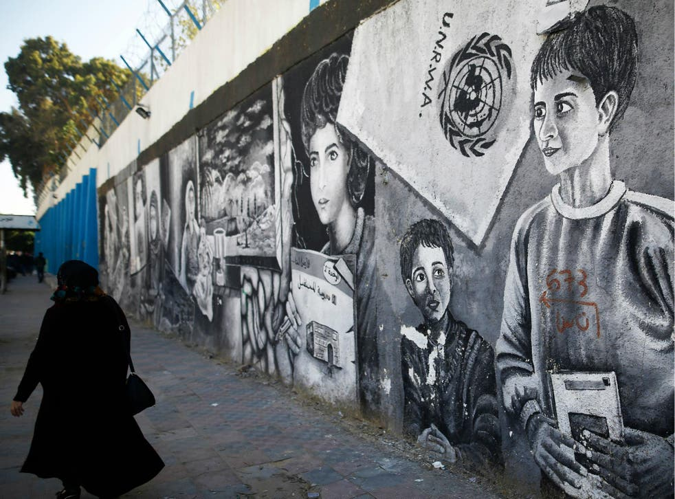 A Palestinian women walks past graffiti painted on the wall of the building of the UNRWA headquarters in Gaza City on 8 January 2018.