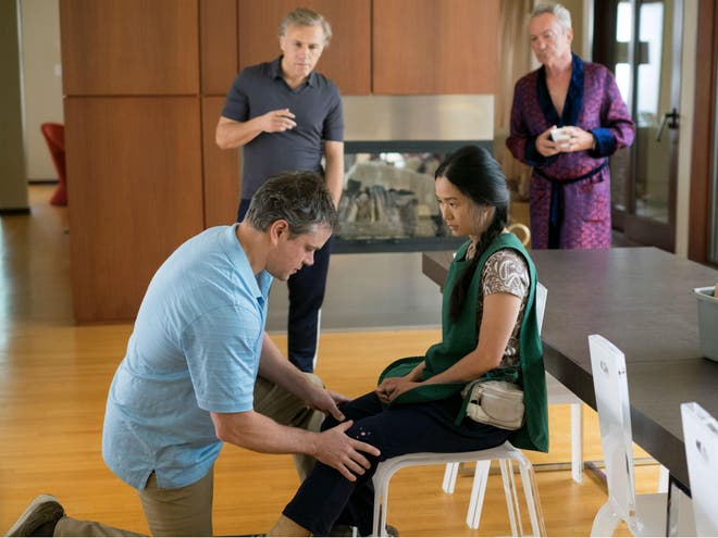 A scene from 'Downsizing' where Mat Damon is on one knee touching Hon Chau's knee with his hands as she is on a chair because she is an amputee. She is looking at Mat as he is facing at her legs.