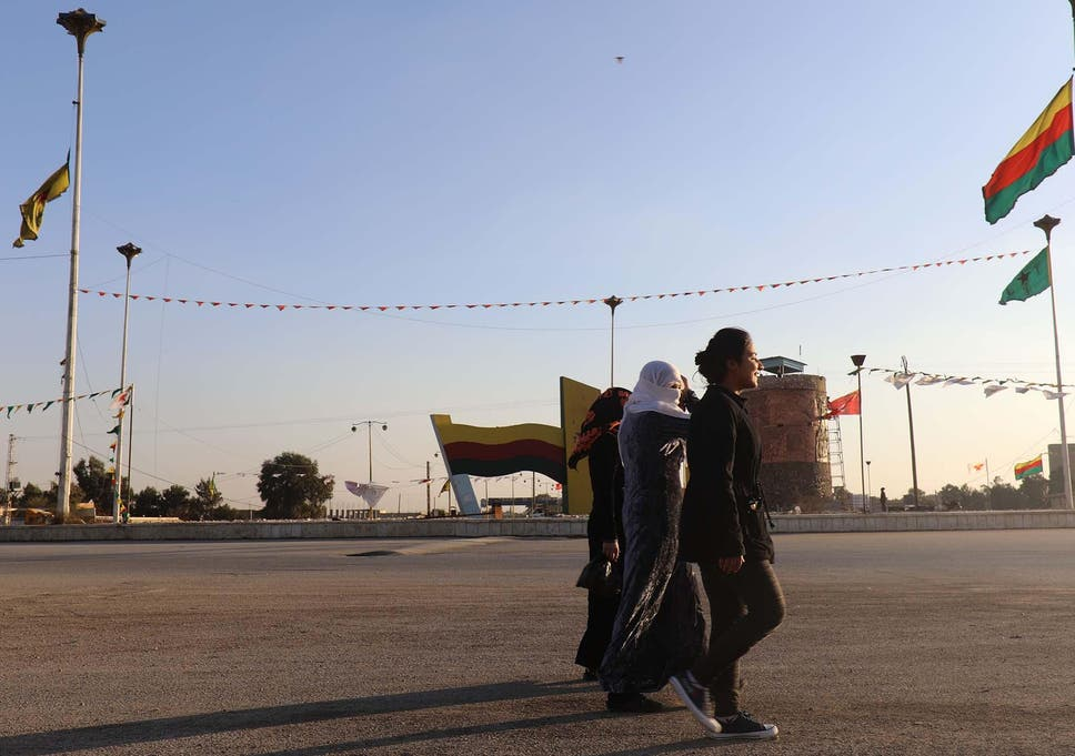 36197b83fe5 Syrian Women walk in a street next to Kurdish flags in the Syrian town of  Hasakah