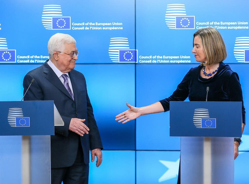 The Palestinian President Mahmoud Abbas (L) and EU High Representative for Foreign Affairs Federica Mogherini (R) shake hands at the end of a joint statement