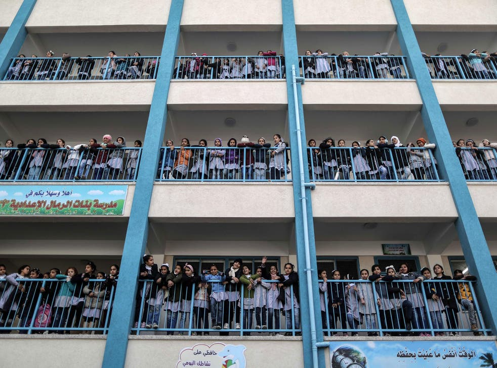 Palestinian schoolgirls pose for a group picture outside their classrooms at a school belonging to the United Nations Relief and Works Agency for Palestine Refugees (UNRWA) in Gaza City on 22 January 2018