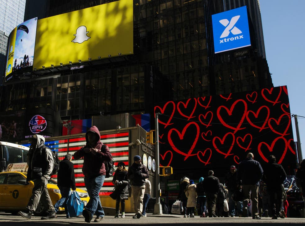 Pedestrians cross the street below a billboard displaying the logo of Snapchat above Times Square in New York March 12, 2015
