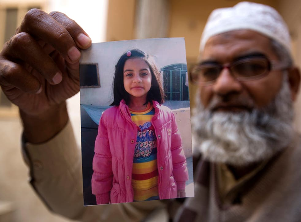 Zainab Ansari's father Mohammed Amin holds up a picture of his daughter