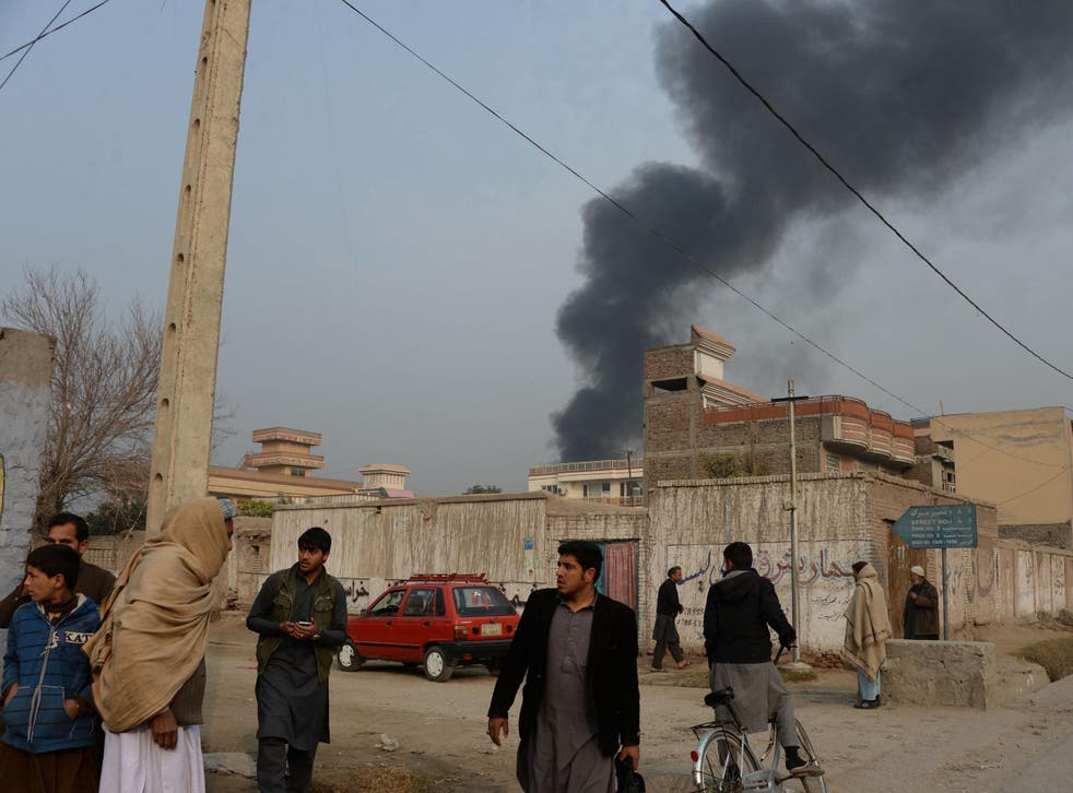 Afghan civilians gather on a street next to a plume of smoke coming from the area around an office of the British charity Save the Children during an ongoing attack in Jalalabad on 24 January 2018