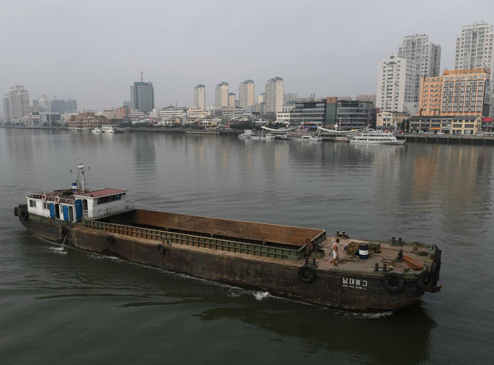 A North Korean ship passes in front of the waterfront of the Chinese border city of Dandong