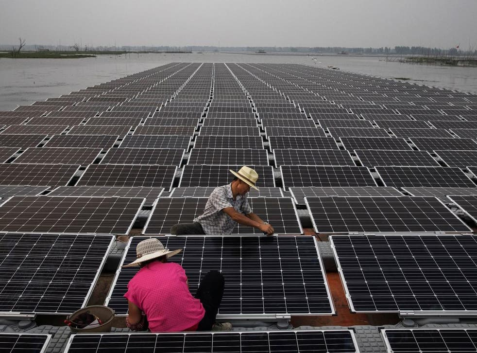 Workers prepare panels on the Chinese solar farm
