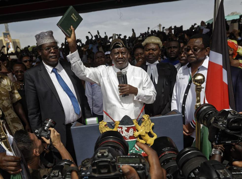 Opposition leader Raila Odinga holds a Bible aloft after professing an oath during his mock swearing-in ceremony