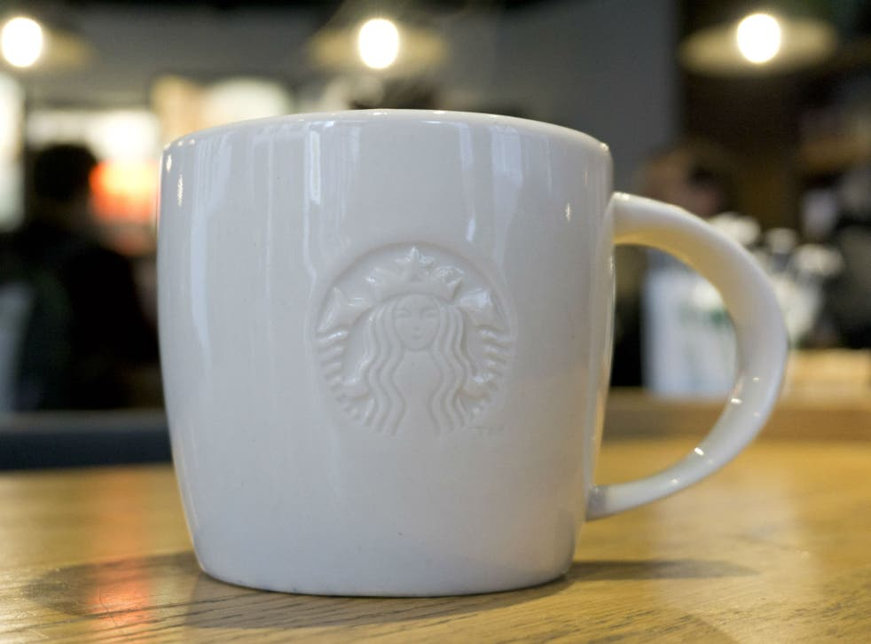 A mug of coffee is pictured above a Starbucks coffee shop