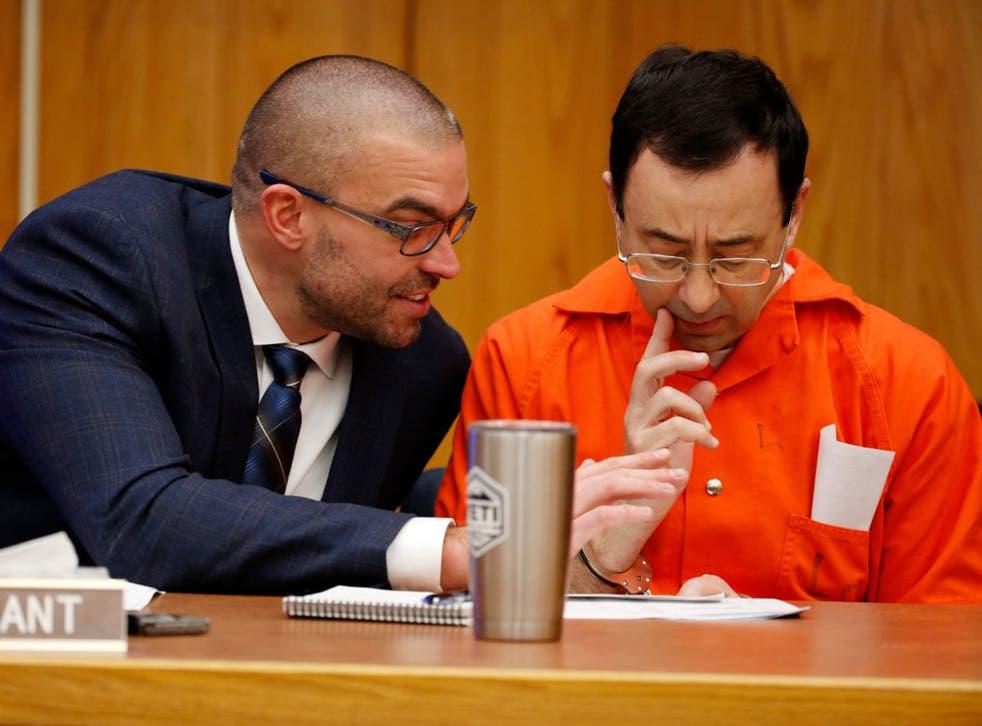 Larry Nassar talks to his defence attorney Matt Newberg (left) in court yesterday