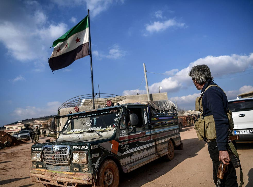 A Turkish-backed Syrian rebel fighter stands guard at a checkpoint in the Syrian town of Azaz on a road leading to Afrin