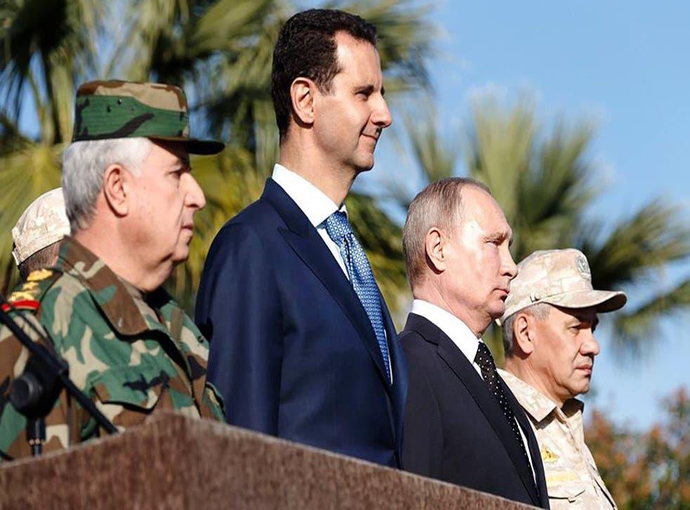 Bashar al-Assad and Vladimir Putin inspect a military parade in the northwestern Syrian province of Latakia