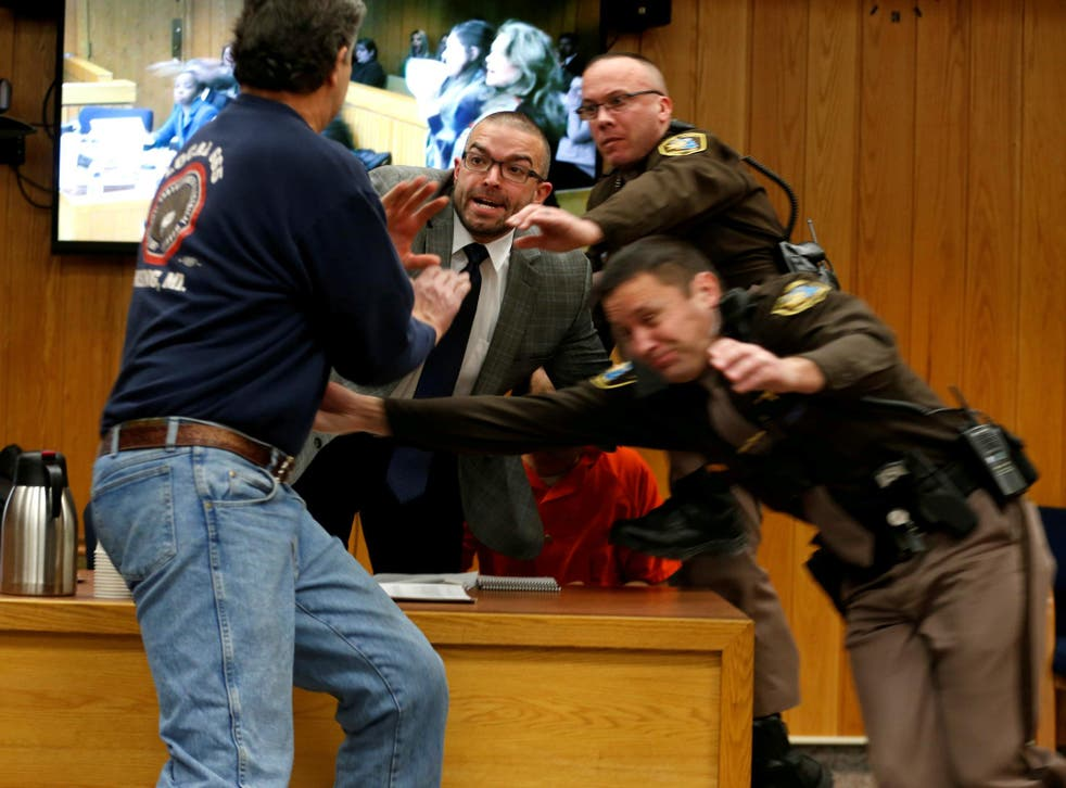 Randall Margraves (L) lunges at Larry Nassar (wearing orange) a former team USA Gymnastics doctor on 2 February 2018. Nassar has been sentenced to more than 175 years in jail.