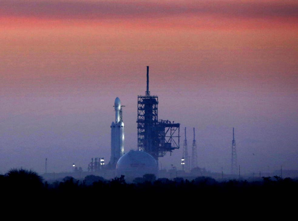 Enveloped in morning fog, the SpaceX Falcon Heavy sits on launchpad 39A at first light, in this view from Playalinda Beach, Florida