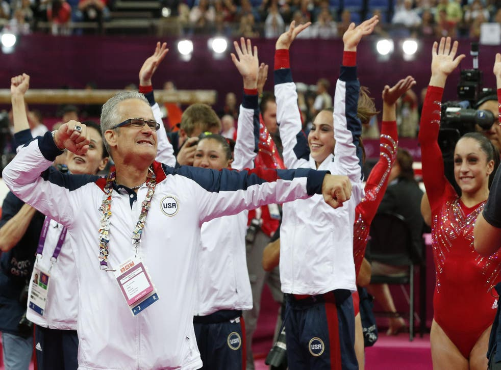 US women gymnastics team's coach John Geddert celebrates with the team after the artistic gymnastics event of the London Olympic Games