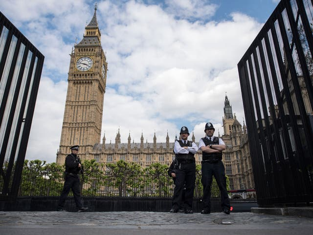 Armed police officers stand guard outside the Houses of Parliament