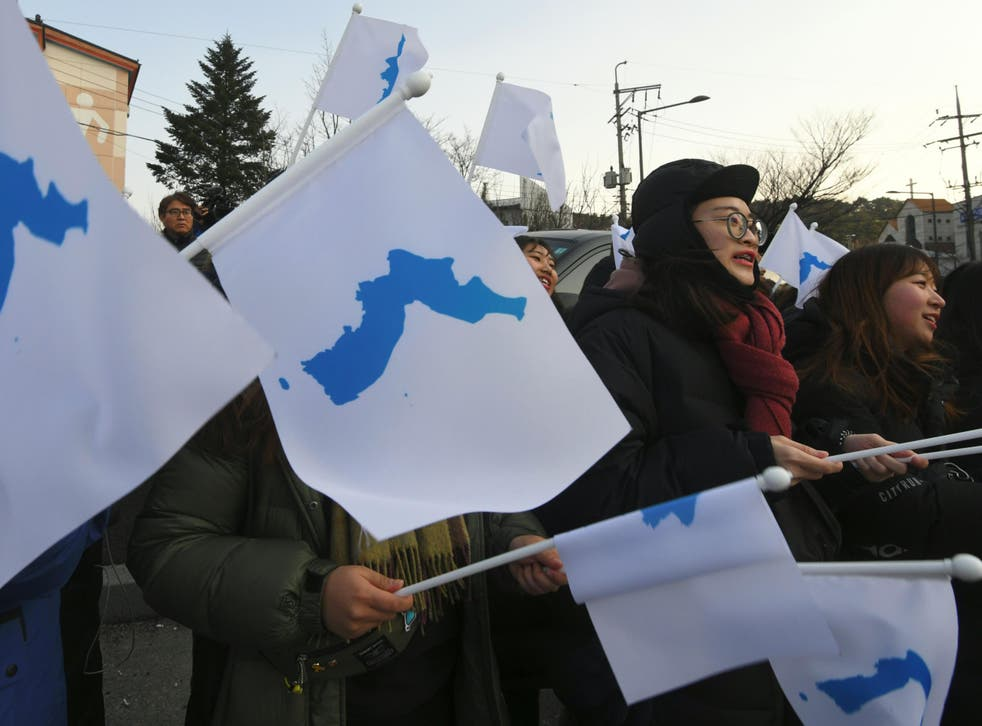 South Korean supporters wave 'unification flags' as they welcome North Korea's art performers to Gangneung, the host city of the ice venues for the Pyeongchang Winter Olympic Games